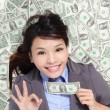 Business woman show ok with money bed — Stock Photo