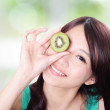 Royalty-Free Stock Photo: Woman holding kiwi fruit cover her eyes