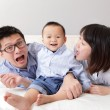 Family lying on bed with funny facial expression — Stock Photo