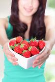 Beautiful woman showing fresh strawberries — Stock Photo