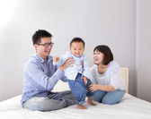 Happy family playing on white bed — Stock Photo
