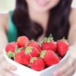 Beautiful woman showing fresh strawberries — Stock Photo