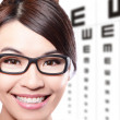 Stock Photo: Womwith glasses and eye test chart