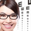 Foto de Stock  : Womwith glasses and eye test chart