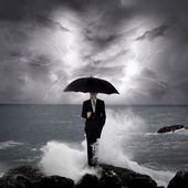 Business man under an umbrella in the sea — Stock Photo