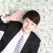 Happy businessman lying on money bed — Stock Photo