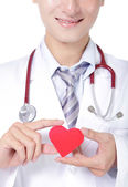Doctor holding a red love heart pillow — Stock Photo
