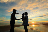 Family watching the sunrise on the beach — Stock Photo