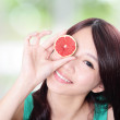 Woman holding grapefruit cover her eyes — Stock Photo