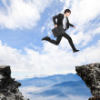 Businessman jumping over danger precipice — Stock Photo