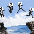 Stock Photo: Businessmjumping with GOAL text on danger precipice