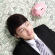 Happy businessman look pink piggy bank  — Photo