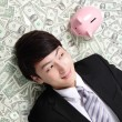 Happy businessman look pink piggy bank — 图库照片