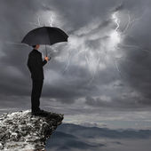 Business Man with umbrella look rainstorm cloud — Stock Photo
