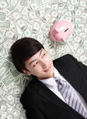 Happy businessman look pink piggy bank — Stock Photo