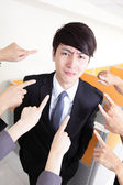 All hands finger pointing at a businessman — Stock Photo
