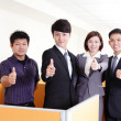 Business group smiles and showing thumb up — Stock Photo