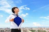 Business man showing superhero suit — Stock Photo