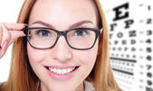 Woman with glasses and eye test chart — Stock Photo