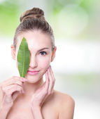 Beautiful woman face portrait with green leaf — Stock Photo