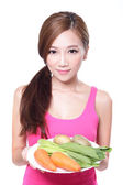 Woman holding green vegetables and carrots — Stock Photo