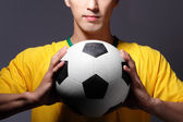 Sport man smiling and holding soccer ball — Stockfoto