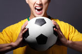 Excited sport man shouting and holding soccer ball — Stock Photo