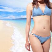 Woman in blue bikini at sea beach — Stock Photo