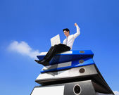 Business man using notebook computer and sitting on lots piles of document folders — Stock Photo