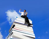 Happy business man using tablet pc computer and sitting on a stack Of Books — Foto de Stock
