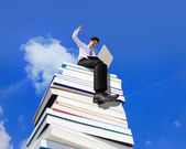 Happy business man using pc computer and sitting on a stack Of Books — Foto de Stock