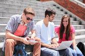Happy students using digital tablet — Stock Photo