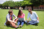 Happy College students using computer — Stock Photo
