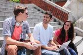 Happy students using digital tablet — Stockfoto