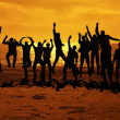 Stock Photo: Male friends are having fun and jumping up on sunset