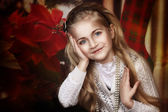 Beautiful little girl holding her hands near the face on christmas style background — Stock Photo