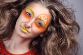 Closeup portrait of young female with orange fantasy makeup on grey background — Stock Photo