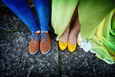 Couples legs dressed in bright colorful shoes — Stock Photo