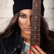 Confident looking female holding guitar near her face standing in front of white brick wall — Stock Photo