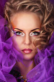 Portrait of caucasian attractive young woman in purple lace and net with fantasy style makeup and blond curls looking straight to the camera — Stock Photo