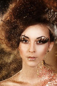 Portrait of beautiful female on carnival in golden shimmery glitter and sparkles looking to the camera — Stock Photo