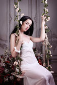 Beautiful brunette is sitting on the floral swing on the gray vintage background — Stockfoto
