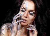 Closeup portrait of beautiful young brunette with long feather lashes in silver liquid paint and foil on black background holding her hands near her face — Stock Photo