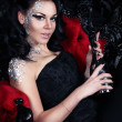 Beautiful seductive brunette is sitting in red gothic chair and holding a silver bottle of champagne. — Stock Photo #38593129