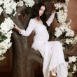 Stock Photo: Beautiful pregnant brunette womis sitting in flower tree and looking to camera