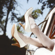 Постер, плакат: Slim pretty brides legs in white leather heels out of the vintage wedding cars window