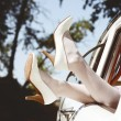 Stock Photo: Slim pretty brides legs in white leather heels out of vintage wedding cars window