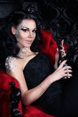 Beautiful seductive brunette is sitting in red gothic chair and holding a silver bottle of champagne. — Stock Photo