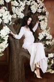 Beautiful pregnant brunette woman is sitting in the flower tree and looking to the camera — Stock Photo