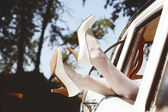 Slim pretty brides legs in white leather heels out of the vintage wedding cars window — Stock Photo